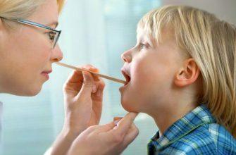 Доктор смотрит горло у ребенка